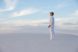 man standing alone on a sand dune
