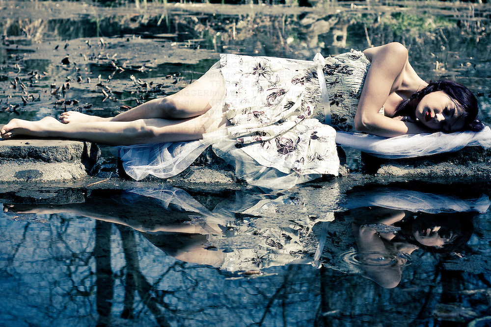Young adult female sleeping beside lake with reflections