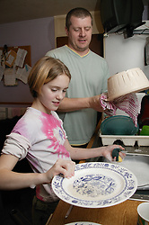 Young girl helping her father do the washing up in the kitchen,