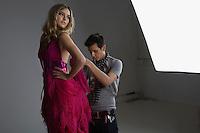 Designer Adjusting Dress Back on Fashion Model