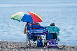 © London News Pictures. 16/08/0216. Aberystwyth, UK. People enjoying a hot summer afternoon at Aberystwyth on the west wales coast UK. The weather is set to improve even more tomorrow, culminating in a mini-heatwave, with temperatures forecast to reach the high 20s or low 30s centigrade in parts of the UK. Photo credit: Keith Morris/LNP