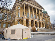 """16 MARCH 2020 - DES MOINES, IOWA: The health screening tent on the west side of the State Capitol in Des Moines. Because of numerous reports of Coronavirus in Iowa, the governor is suspending the legislative session for 30 days. It was scheduled to run until mid-April. Sunday night, the Governor announced that the state health department had recorded """"community spread"""" in Des Moines. As a result the State Capitol instituted mitigation measures that included mandatory health screening for everyone going into the building, canceling group tours of the building, and closing the souvenir shop and snack bar.    PHOTO BY JACK KURTZ"""