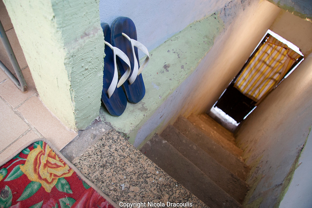 Binho's Flip Flops, entrance to Binho s house 2006. Herbeson Binho Alves Parada de Lucas/Linda Primavera Binho now 27 lived in Parada de Lucas in 2006 he moved to Linda Primavera two years ago partly due to the murder of his father. As with many tragedies in the favela there is still no clear reason for his father's death especially confusing because he had nothing to do with the local drug faction. Binho has been enterprising enough to land himself a job as a digital communications specialist. With a payout from his previous job Binho was able to buy some land in Linda Primavera a suburb just north of Rio de Janeiro his house is the second to be constructed on a street that still has no name. He is currently extending his own house building a house for his brother in law and has plans to also build homes for his mother and mother in law on the same property. Life is much calmer and safer now. <br /> Part of the series Viver no Meio do Barulho (Living in the Middle of the Noise)