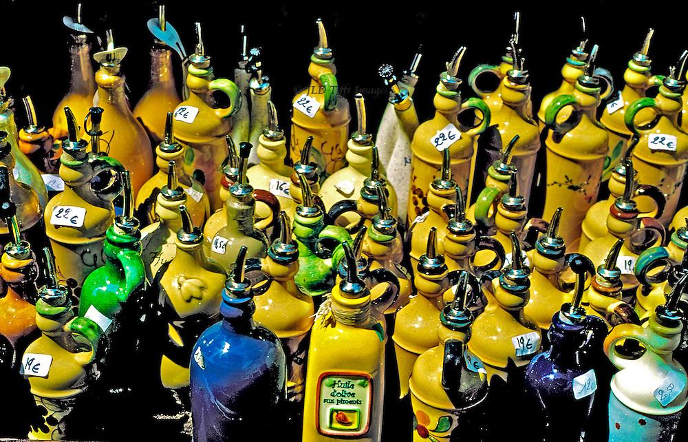Olive oil bottles grouped on sidewalk outside shop, Apt town square..Olive oil bottles grouped on sidewalk outside shop, Apt town square.