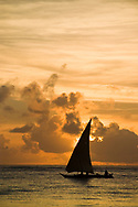 A small group of fishers sail their dhow, a carved wooden boat, in the Indian Ocean. Matemwe, Zanzibar, Tanzania.