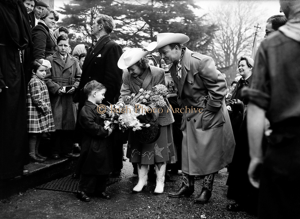 "Roy Rogers 'King of the Cowboys' and his wife Dale Evans when they entertained the boys of St Augustine's School in Obelisk Park, Blackrock, Co. Dublin.19/03/1954..Roy Rogers, born Leonard Franklin Slye (05/11/1911 - 06/07/1998), was an American singer and cowboy actor, one of the most heavily marketed and merchandised stars of his era, as well as being the namesake of the Roy Rogers Restaurants franchised chain. He and his wife Dale Evans, his golden palomino, Trigger, and his German Shepherd dog, Bullet, were featured in more than 100 movies and The Roy Rogers Show. The show ran on radio for nine years before moving to television from 1951 through 1957. His productions usually featured a sidekick, often either Pat Brady, (who drove a Jeep called ""Nellybelle""), Andy Devine, or the crotchety George ""Gabby"" Hayes. Rogers's nickname was ""King of the Cowboys"". Evans's nickname was ""Queen of the West.""."