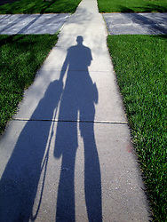 Out walking my dog I glanced down to see our shadows on the sidewalk.  The cross image was a happy accident.