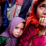 Young girls look in awe at foreigners in an Afghan market in October 2001.