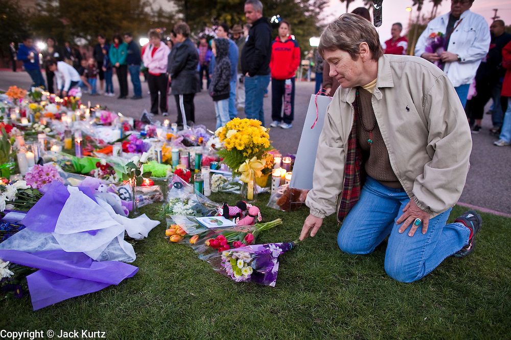 tucsonshooting - 09 JANUARY 2011 - TUCSON, AZ: Tucsonian Nancy Platt (CQ) lays flowers on a memorial for Gabrielle Giffords at University Medical Center in Tucson Sunday night. Congresswoman Gabrielle Giffords, US Federal Judge John Roll and several other people were shot by a lone gunman in a mass shooting Saturday.  ARIZONA REPUBLIC PHOTO BY JACK KURTZ