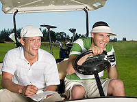 Two young male golfers sitting in cart laughing