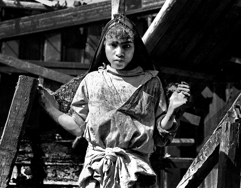 Teen aged boy carrying a pack on his back, hung from a loop over his head, gazes wearily and solemnly at the camera.  He is wrapped in a filthy tunic and surrounded by angled wooden beams.  His sensitive mouth and gentle expression makes one wish better for him.
