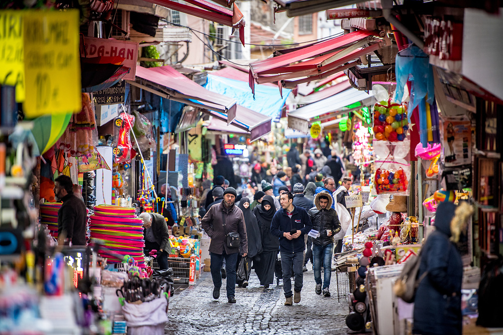 View down a busy narrow street with awnings from shops on either side providing coverage to shoppers, Istanbul, Turkey