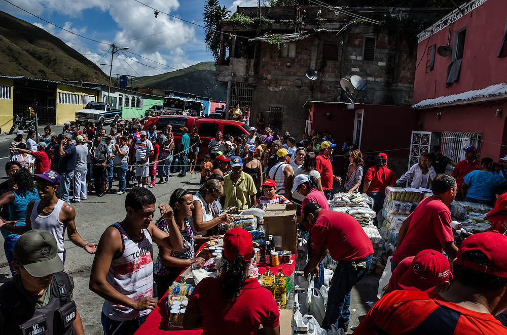 "LOS TEQUES, VENEZUELA - JANUARY 18, 2015: Hundreds of people lined up to purchase difficult to find food items, such as sugar, cooking oil, and rice, at subsidized prices during a government ""Mercal"" event in Los Teques. Despite being a petro-state with one of the largest oil reserves in the world, basic food goods are difficult to find in stores across Venezuela."
