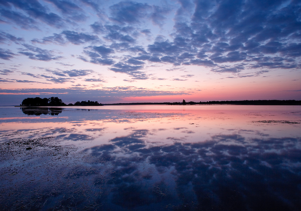 Defined and clear reflections form during an intensely colored beautiful Autumn dawn on  the St Lawrence River  in the Thousand Islands Region, Ontario, Canada. This is also the location of the St Lawrence Islands National Park.