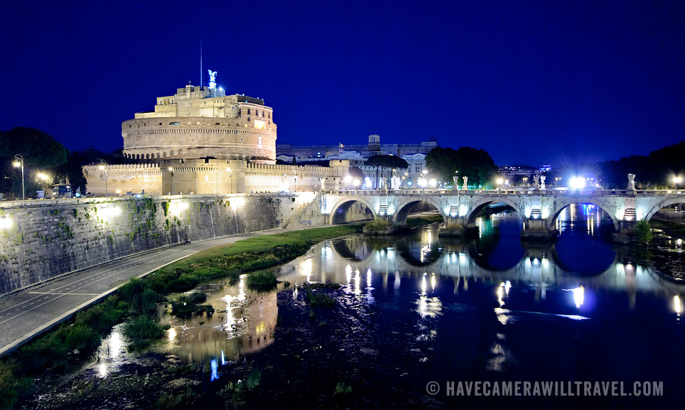 The lights of the Castel Sant'Angelo and the bridge next to it are reflected on the still waters of the Tiber in Rome, Italy.