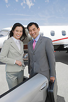 Portrait of mid-adult businesswoman and mid-adult businessman standing in front of private plane.
