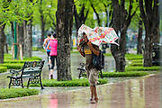 05 MAY 2013 - BANGKOK, THAILAND:  A homeless man walks around Sanam Luang (the royal parade ground) during an unseasonal thunderstorm near the Grand Palace in Bangkok, Thailand. The rainy season in Bangkok is usually mid June through early November, but 2013 has seen unseasonal rains through what is normally Bangkok's dry season.       PHOTO BY JACK KURTZ