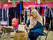 13 DECEMBER 2018 - SINGAPORE:  A woman selling Muslim head scarves in her shop in the Joo Chiat complex. Joo Chiat is a multi-tower high rise residential estate. There are hawker food stalls and retail businesses on the ground floor and residences on the upper levels.  The Geylang area of Singapore, between the Central Business District and Changi Airport, was originally coconut plantations and Malay villages. During Singapore's boom the coconut plantations and other farms were pushed out and now the area is a working class community of Malay, Indian and Chinese people. In the 2000s, developers started gentrifying Geylang and new housing estate developments were built.      PHOTO BY JACK KURTZ