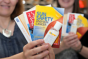 Two unidentified women hold up safety leafets and sun cream warning about the dangers of skin cancer.