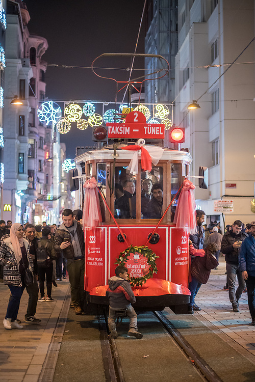 A small boy holds onto the front of a crowded trolley car navigating its way through the streets of Istanbul, Turkey