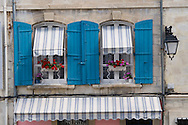 Colourful windows with wooden shutters in Arles, France