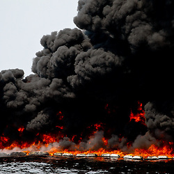 Oil is burned off from the surface during a controlled burn near the source of the BP Plc Deep Water Horizon oil spill site in the Gulf of Mexico off the coast of Louisiana, U.S., on Thursday, July 15, 2010. Photographer: Derick E. Hingle/Bloomberg