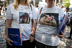 © Licensed to London News Pictures. 06/07/2016. London, UK. ELAINE FAIRLEY (Left) sister of Senior Aircraftsman Peter McFerran and MELINDA INGRAM (right) mother of Senior Aircraftsman Chris Dunmore, hold copies of the Chilcot Report, outside the QE2 conference centre in London where the long-awaited Chilcot inquiry into the war in Iraq has been released. Photo credit: Ben Cawthra/LNP