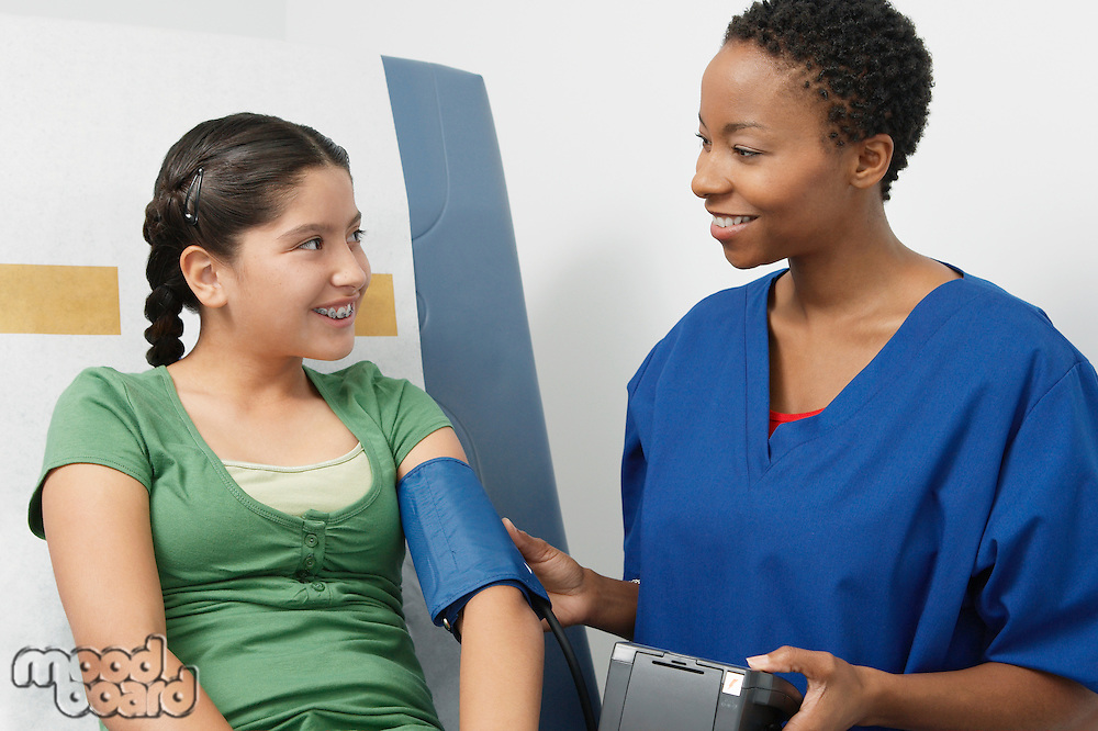 Female nurse taking girls blood pressure in hospital