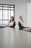 Two women sitting in office and laughing