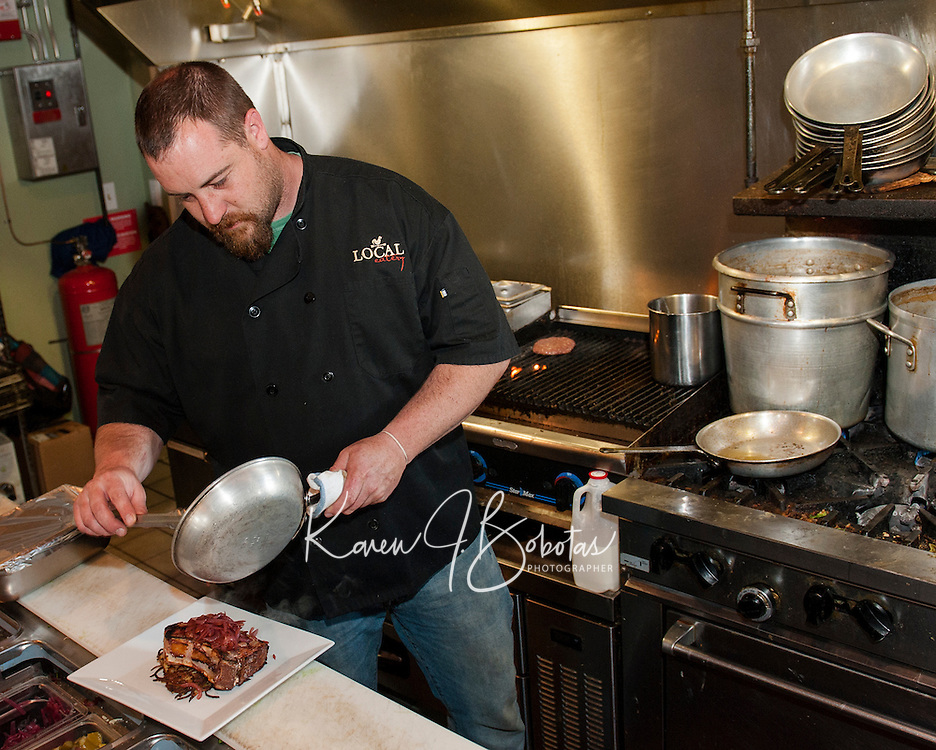 """Chef Kevin Halligan prepares a house-raised smoked pork chop with potato latkes, parsnip apple puree with red onion jam during """"Restaurant Week"""" at The Local Eatery on Tuesday evening.   (Karen Bobotas/for the Laconia Daily Sun)"""