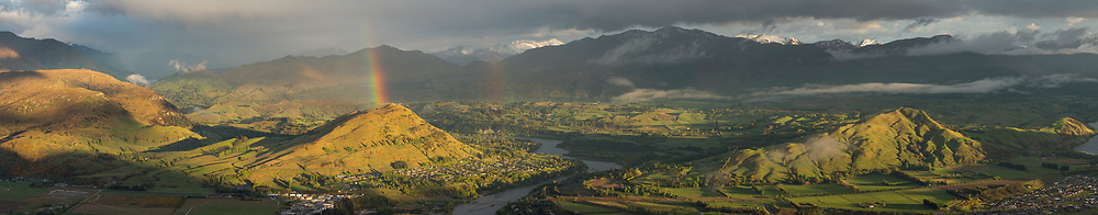 A rainbow over Ferry hill beside the Shotover River in this panoramic view of the Queenstown area.
