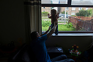 Simon Giles holds his son Oliver-James Giles in the living room of the house the family rents in Bradford, Great Britain Monday, May 26, 2014. Through Save the Children's EAT, SLEEP, LEARN AND PLAY programme the family was awarded a fridge freezer and a toy and book pack. A record five million children in the UK could be trapped in poverty by 2020, according to new research by Save the Children. The report reveals that children have paid the highest price in the recession, with families having been hit by years of flat wages, cut to benefits and the rising cost of living. (Elizabeth Dalziel for Save the Children )