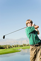 Young Man Swinging Golf Club