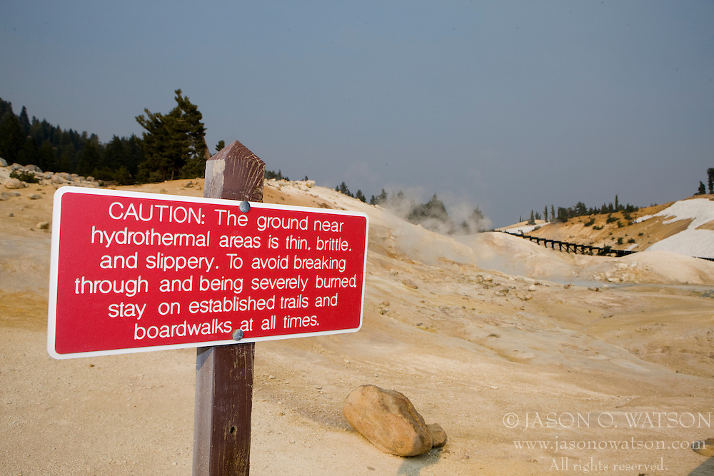 A red caution sign warns visitors to say on the boardwalk to avoid damage to the hydrothermal areas in Bumpass Hell, Lassen Volcanic National Park, California, USA.