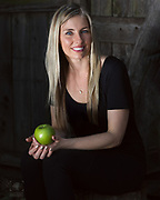 Sunlight portrait of attractive female health food entrepreneur holding a green apple.