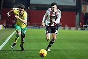 Norwich City defender Ivo Pinto (25) and Brentford defender Tom Field (30) chasing the ballduring the EFL Sky Bet Championship match between Brentford and Norwich City at Griffin Park, London, England on 31 December 2016. Photo by Matthew Redman.