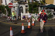 Olympic Games Maker volunteer crossing a blocked road near Hampton Court, Southwest London. London 2012 volunteers are called 'Games Makers', as they are helping to make the Games happen. Up to 70,000 Games Makers take on a wide variety of roles across the venues: from welcoming visitors; to transporting athletes; to helping out behind the scenes in the Technology team to make sure the results get displayed as quickly and accurately as possible. Games Makers come from a diverse range of communities and backgrounds, from across the UK and abroad. The vast majority are giving up at least 10 days to volunteer during the Games..