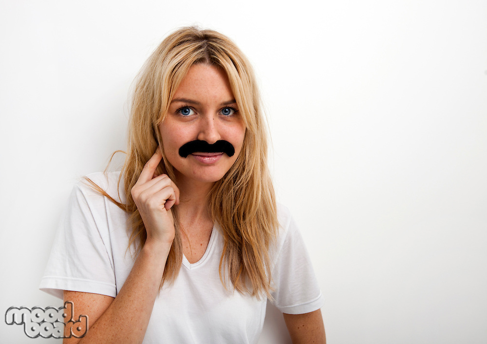 Portrait of woman in fake mustache against white background