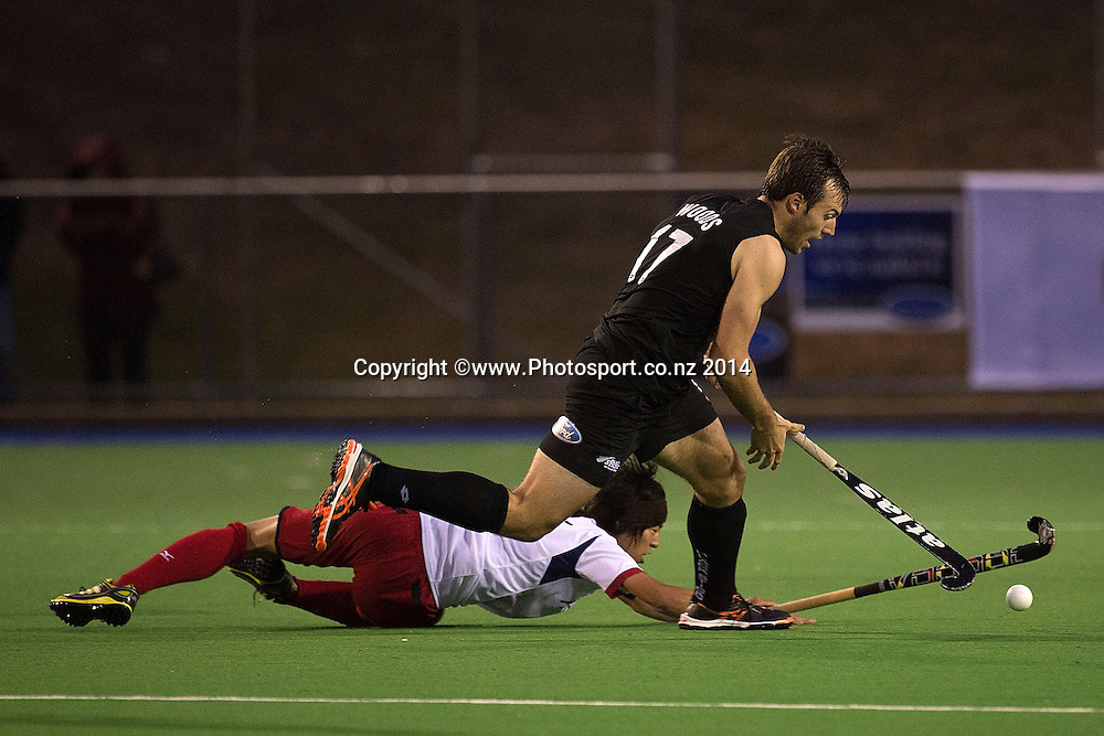 Kazuma Murata (Bottom) of Japan goes down in a tackle by Nic Woods of New Zealand during the Black Sticks Men v Japan international hockey match at the Coastlands Kapiti Sports Turf in Paraparaumu on Friday the 21st of November 2014. Photo by Marty Melville/www.Photosport.co.nz