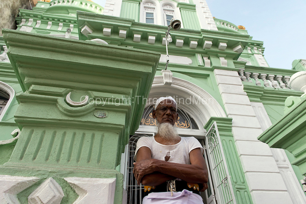 Man at entrance to Mosque on Messenger Street, Colombo.