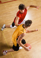 Two young men playing basketball on indoor court