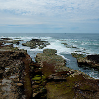Rocky sea shore with blue summer sky with light cloud
