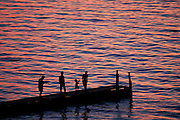 Ribbons of color from a magenta sunset and blue overhead sky reflect from the rippling surface of Lake Mendota as a group of silhouetted people go fishing from a pier at the University of Wisconsin-Madison's Memorial Union Terrace in 1994..