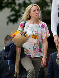 © Licensed to London News Pictures. 07/07/2015. London, UK. A woman carrying flowers. A church service held at St Paul's Cathedral In London on the 10th anniversary of the 7/7 bombings in London which killed 52 civilians and injured over 700 more.  Photo credit: Ben Cawthra/LNP