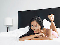 Woman in underwear reclining on bed