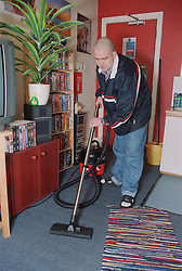 Male resident hoovering bedroom in homeless hostel for people with learning difficulties,
