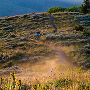 Andrew Whiteford rides towards the sunset on Munger Mountain near Wilson, Wyoming during summer in the Tetons.