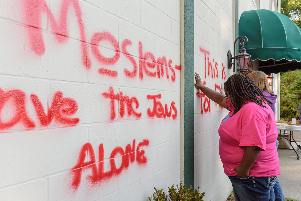 Whitney Franklin and Liz Herrick, students at the Louisville Presbyterian Theological Seminary, pray Thursday, Sept. 17, 2015 at a wall vandalized with graffiti at the Louisville Islamic Center on River Road Wednesday night.