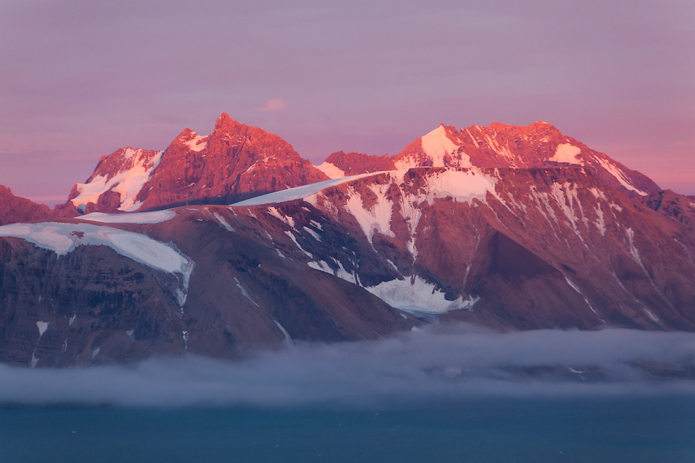 Hornsundtind, the highest peak in southern Spitsbergen (1431 meters), rises above the waters of Hornsund, Svalbard at sunset.