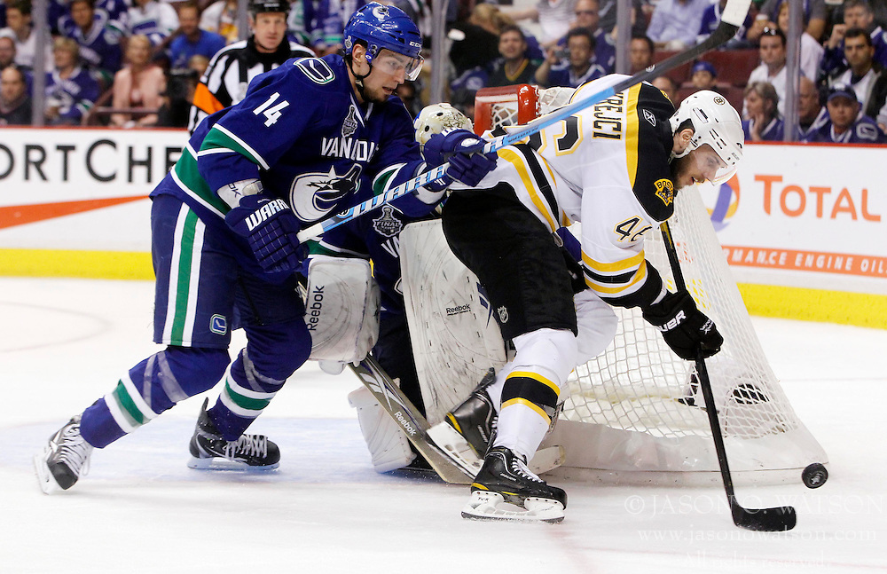 June 4, 2011; Vancouver, BC, CANADA; Boston Bruins center David Krejci (46) battles for the puck with Vancouver Canucks left wing Alex Burrows (14) during the second period in game two of the 2011 Stanley Cup Finals at Rogers Arena. Mandatory Credit: Jason O. Watson / US PRESSWIRE